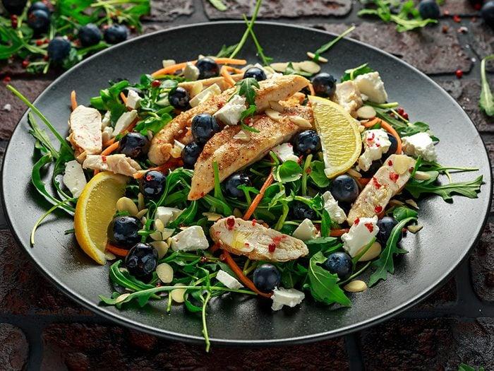 Salade à l'épinard, aux bleuets, à la fêta et aux amandes, sauce aux baies et à la menthe.