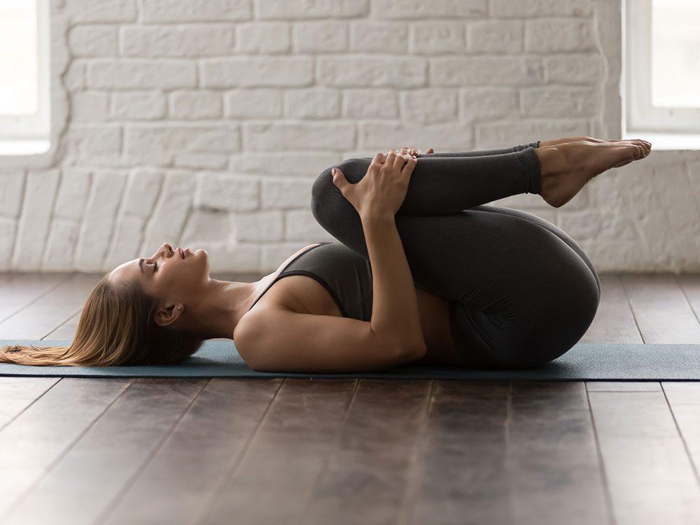 Essayez la posture de yoga du vent pour retrouver de l'énergie.