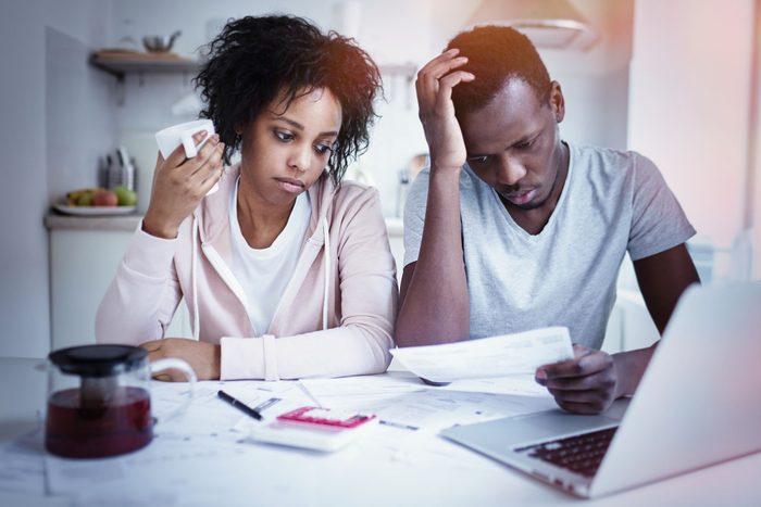 Couple préoccupé qui tente de faire un budget, devant un écran d'ordinateur.