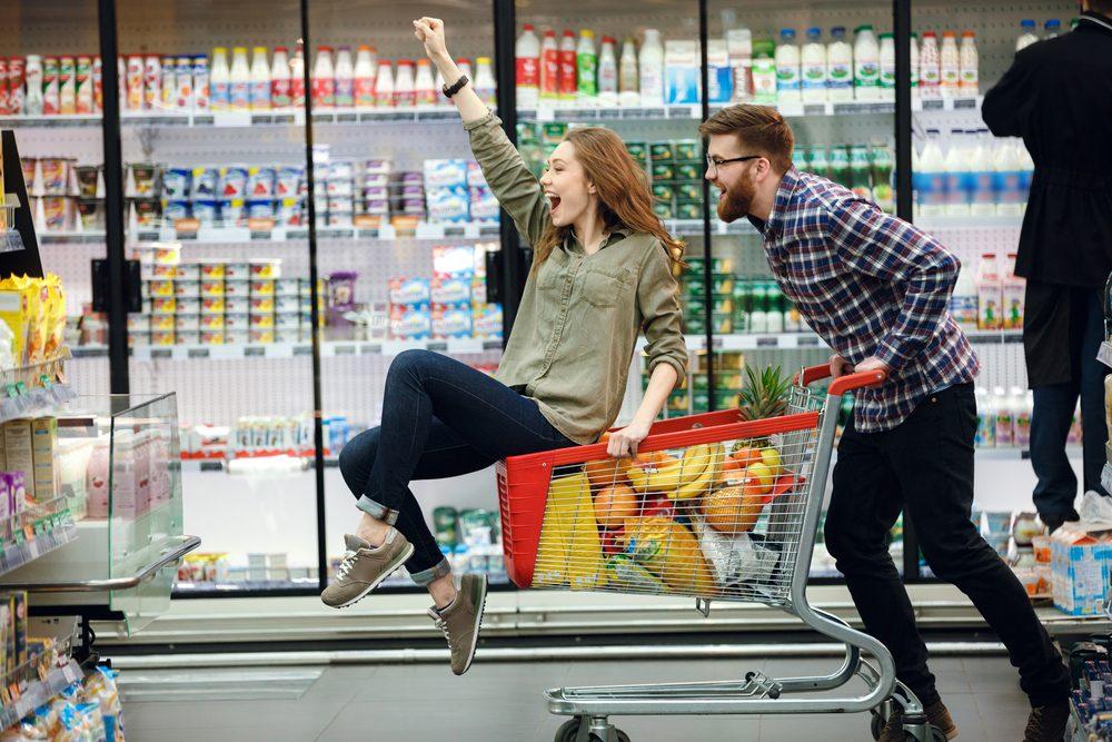 Couple qui s'amuse en faisant l'épicerie