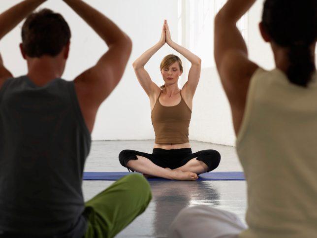 Professeur de yoga devant la classe, les mains au-dessus de sa tête.