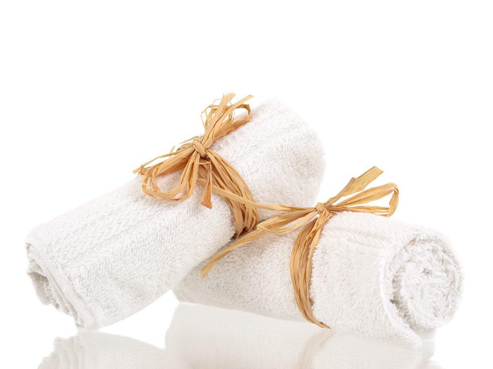 Des serviettes enroulées sur un support à bouteilles de vin