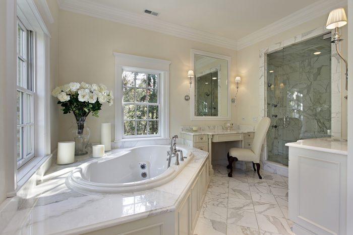 Rénover sa salle de bain avec des luminaires qui se projettent au-dessus de l'armoire à pharmacie.
