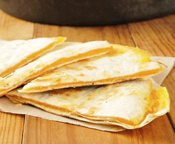 Une tortilla de blé entier saupoudrée de 60g de fromage cheddar râpé, faible en gras