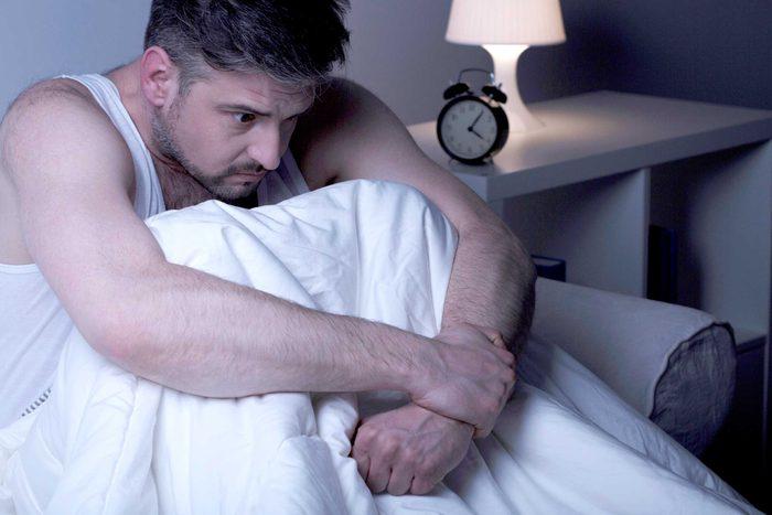 Homme assis sur son lit et qui semble éprouver des remords.