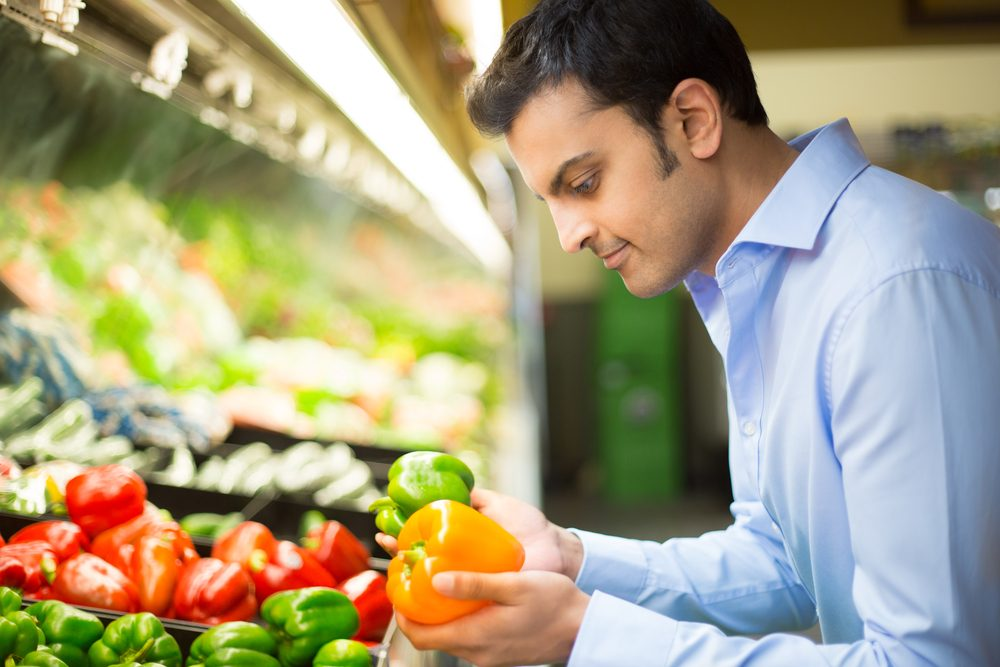 Les fruits et légumes sont manipulés en épicerie.