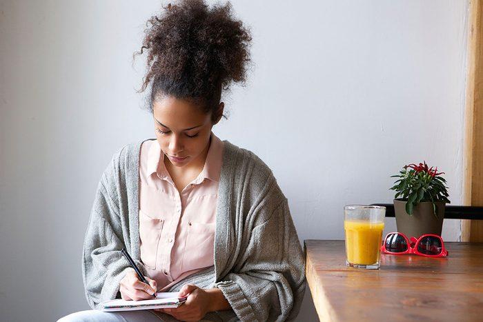 Jeune femme concentrée qui écrit dans son cahier.