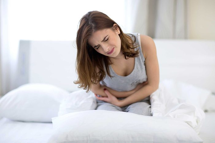Femme dans son lit qui éprouve des douleurs abdominales.