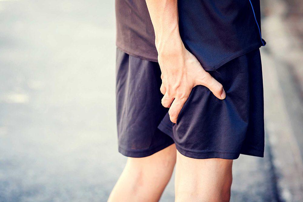 Un homme qui souffre d'une crampe dans la jambe.