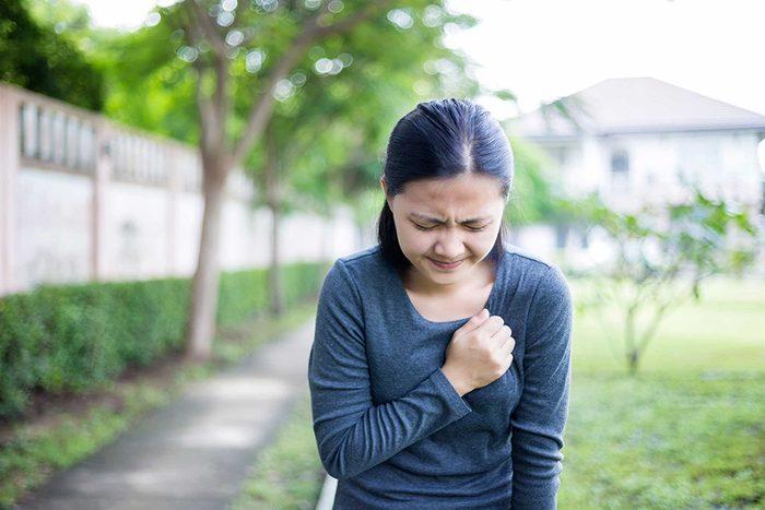 Une femme, dans un parc, qui éprouve une douleur à la poitrine.