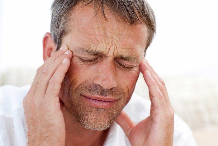 Un homme qui a un mal de tête insoutenable.
