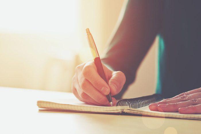 Gros plan sur la main d'une personne qui écrit dans un cahier.