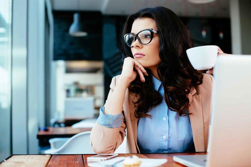 Jeune femme pensive assise à son bureau.