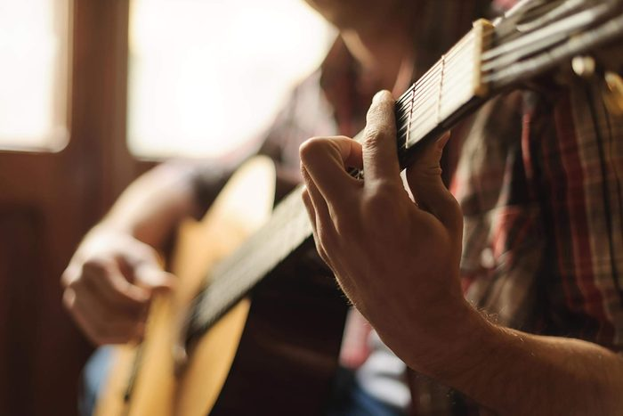 Gros plan sur les mains d'un guitariste et de sa guitare.
