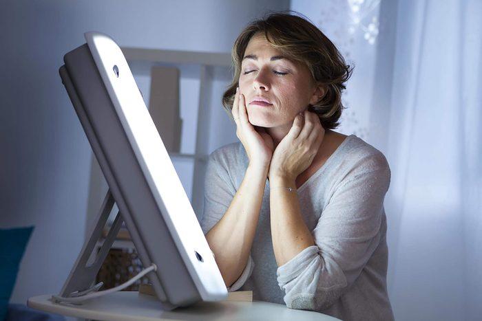 Femme qui se détend devant une lampe pour une séance de luminothérapie.