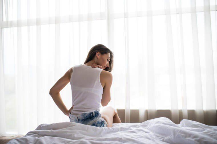 Femme assise sur son lit.
