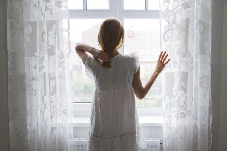 Femme seule devant sa fenêtre, la main sur un rideau.