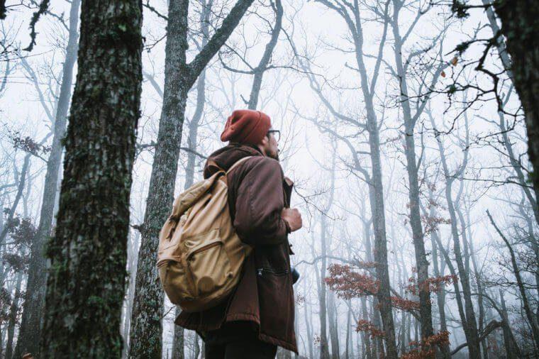 Homme qui marche dans la nature avec un sac a dos.