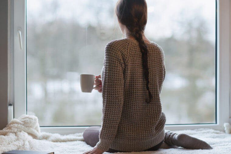 Femme seule devant une fenêtre qui tient une tasse de café.
