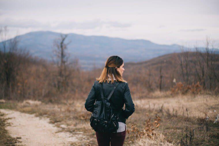 Femme seule qui marche sur un sentier.
