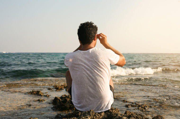 Homme seul assis sur le sable devant la mer.