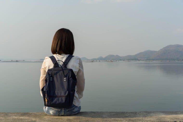 Femme seule assise au bord de l'eau.