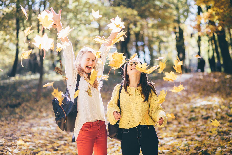 Deus jeunes filles s'amusent avec les feuilles. Rire et joie au rendez-vous.