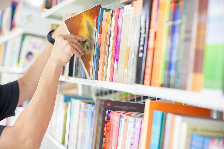 Rangée de livres à la bibliothèque: un utilisateur prend un ouvrage.