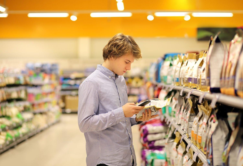 Personne consultant le prix de la nourriture sur un sac à l'animalerie.