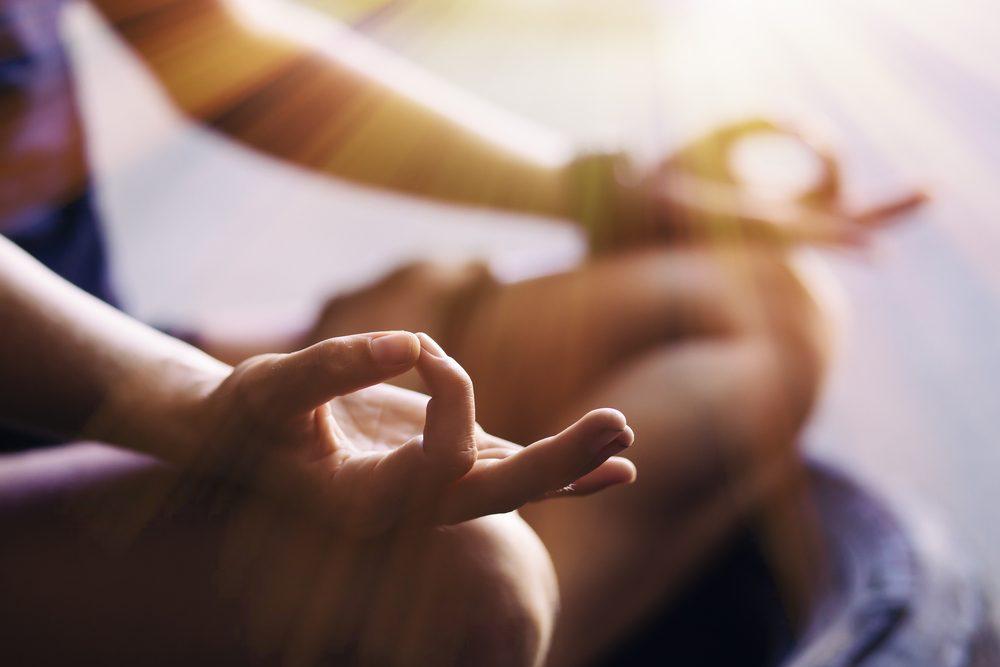 Personne qui pratique la méditation: gros plan sur ses mains.