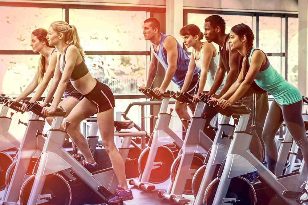 Personnes dans une salle de gym qui font du vélo stationnaire.
