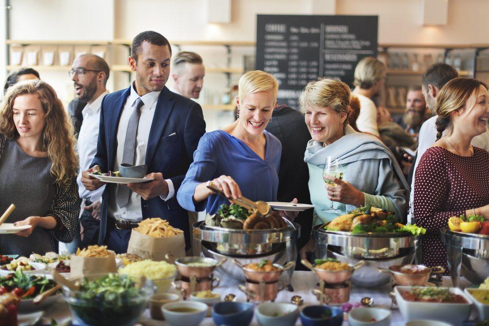 Groupe de gens autour d'un buffet qui discutent.