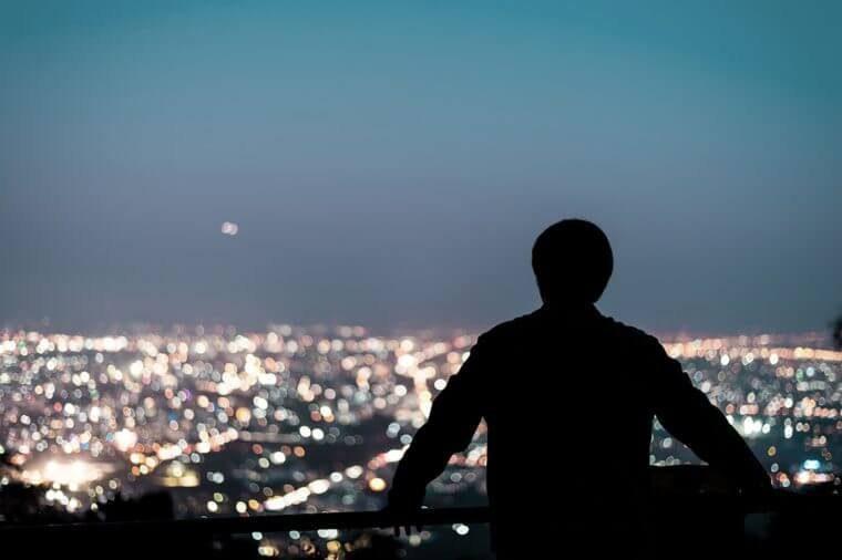 Homme qui regarde la ville à la tombée de la nuit.