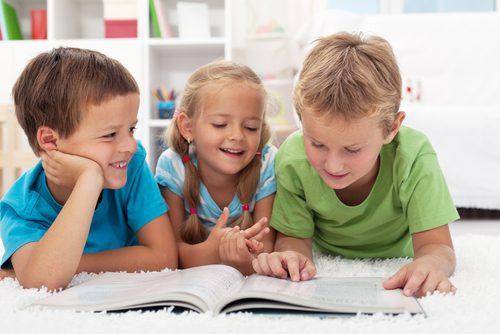 Trois enfants qui regardent un livre.