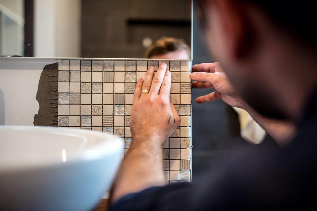 Personne qui refait les tuiles de la salle de bain.