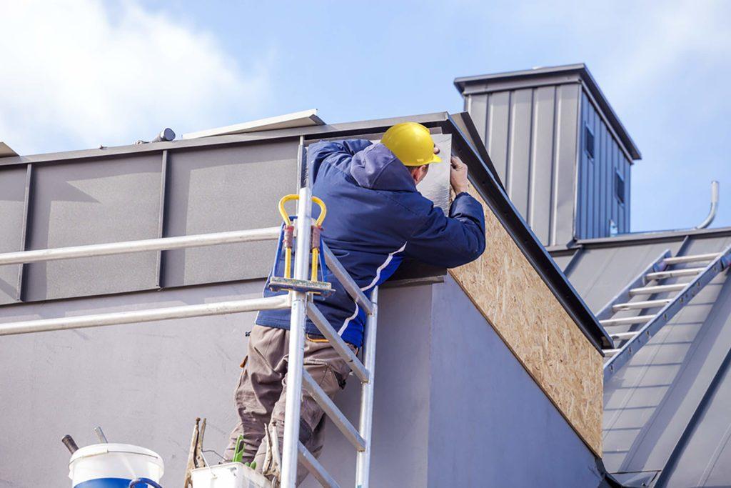 Ouvrier en train de refaire le toit d'une maison.