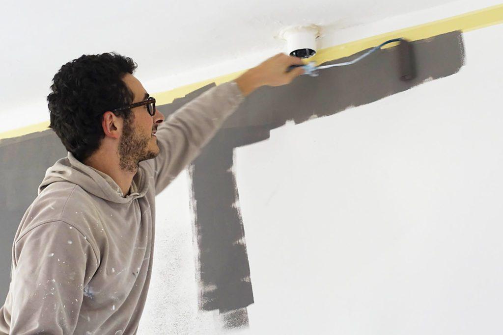 Ouvrier en train de peindre un mur.