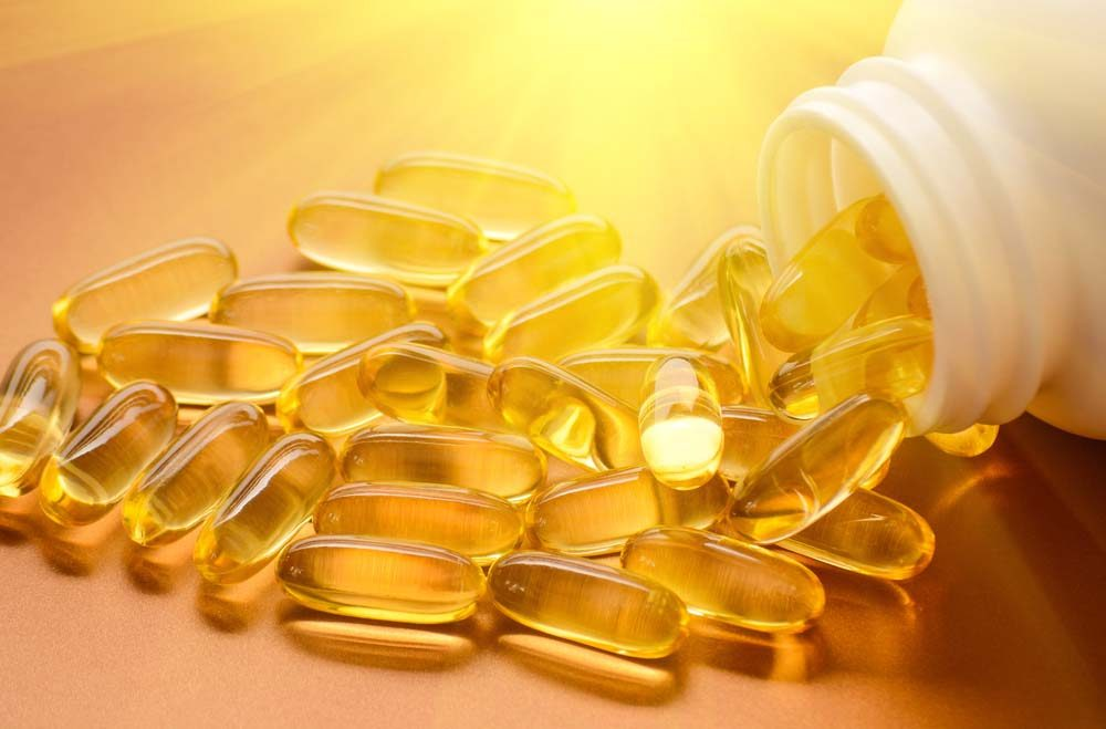Gélules de vitamines D illuminées par un rayon de soleil.