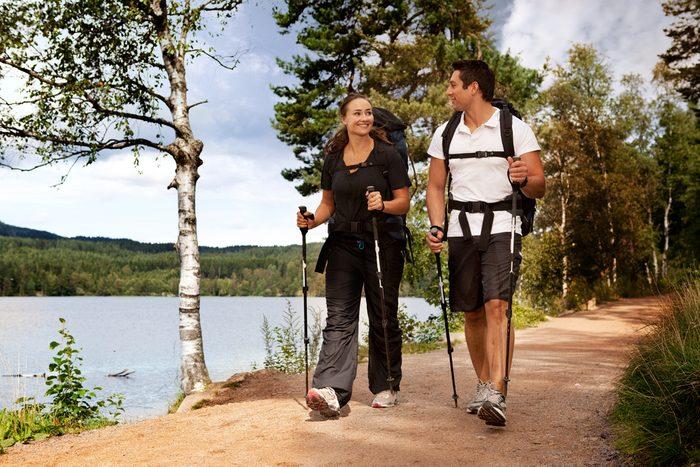 Un couple qui fait une randonnée en longeant un point d'eau.