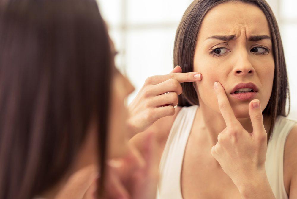 Femme qui se regarde dans le miroir.