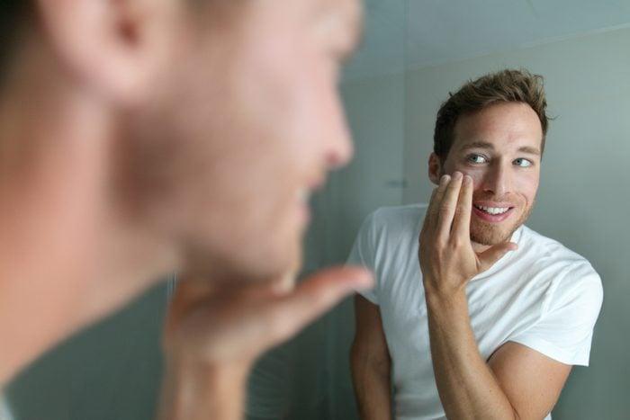 Jeune homme qui se regarde dans le miroir et qui semble satisfait.