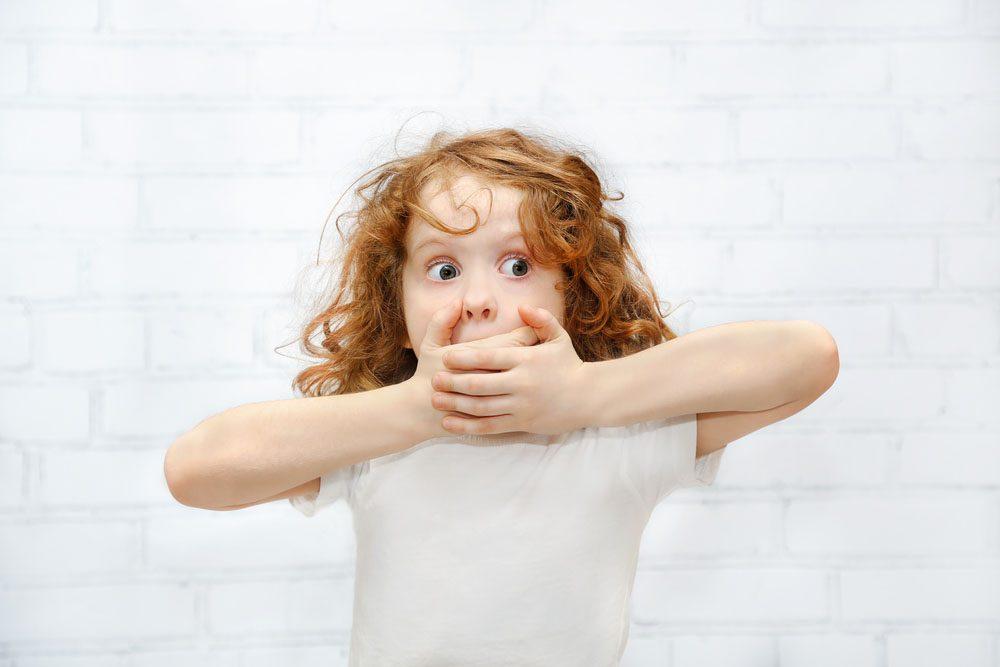 Petite fille qui met ses mains devant sa bouche, car elle vient de faire une bêtise.