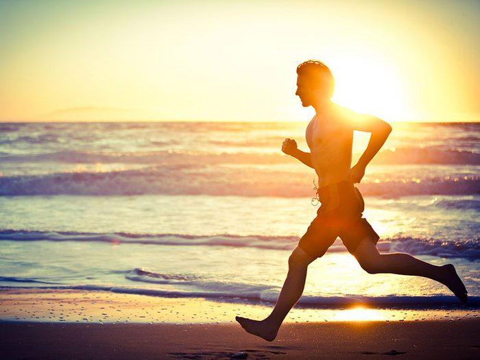 Homme qui court au bord de la mer avec un soleil levant en arrière plan.
