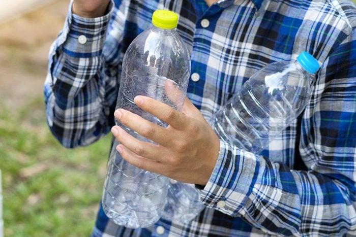 Éliminer les mauvaises herbes avec des bouteilles en plastique.