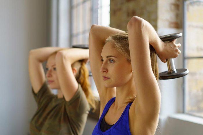 Pour muscler ses bras, faites des extensions avec des haltères.