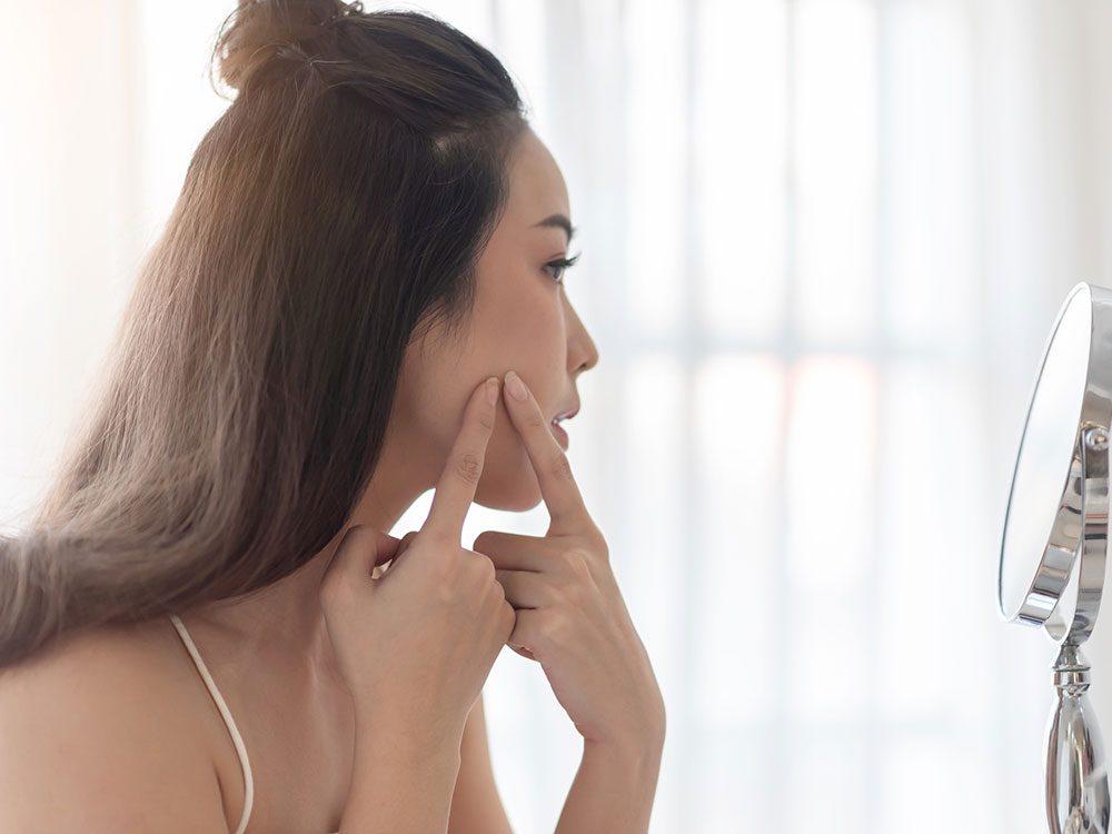 Jouer avec ses boutons peut obstruer les pores de la peau.