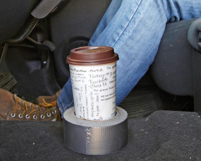 Trucs rénovation: un simple rouleau de ruban adhésif suffit à faire tenir votre gobelet en voiture.