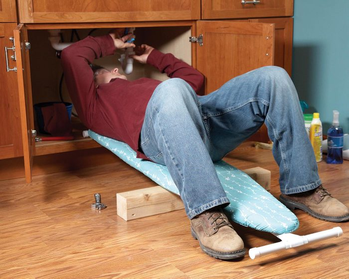 Trucs rénovation: placez une planche à repasser sous votre dos pour éviter de vous faire mal.