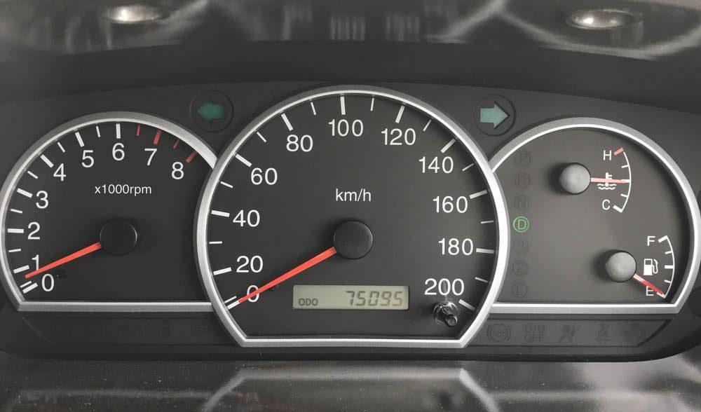 Dans un garage, un mécanicien explique a un client à quoi sert un compteur de vitesse.