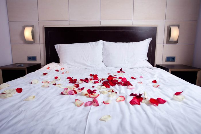 Idée romantique : étaler des pétales de roses sur le lit.